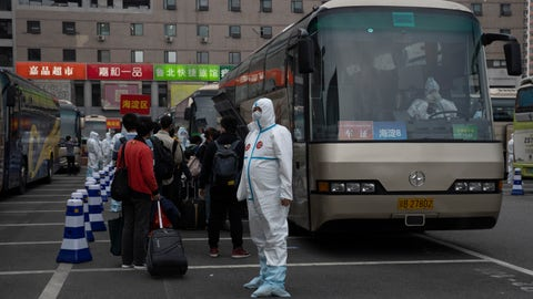 <p>               A worker in protective clothing waits to guide passengers from Wuhan to board buses after they arrive on a high speed train in Beijing on Sunday, April 19, 2020. Wuhan, the city at the center of the global coronavirus epidemic, lifted a 76-day lockdown early April and allowed people to leave for destinations across China. (AP Photo/Ng Han Guan)             </p>