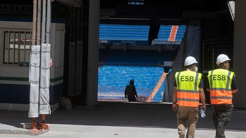 <p>               Workers walk into Real Madrid's Santiago Bernabeu stadium in Madrid, Spain, Monday, May 25, 2020. Spanish league clubs are now allowed to train with groups of up to 14 players as the league stays on track to restart in less than three weeks. (AP Photo/Paul White)             </p>