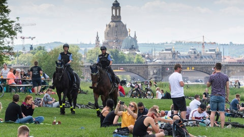 <p>               Two police officers on horses patrol between visitors of a beer garden in Dresden, Germany, Thursday, May 21, 2020. Due to the new coronavirus outbreak people are asked to keep a distance of minimum 1,5 meters (5-feet) between each other in public. The building in the background is the famous 'Frauen Kirche'.  (Robert Michael/dpa via AP)             </p>