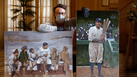 """<p>               In this Wednesday, April 29, 2020, photo, Brooklyn-based baseball artist Graig Kreindler poses with two of his paintings of Babe Ruth, both unfinished, in the lobby of his residence in New York. Over 200 of Kreindler's paintings form the bulk of the exhibit """"Black Baseball in Living Color:The Art of Graig Kreindler,"""" at the Negro Leagues Baseball Museum in Kansas City, Mo. The museum is closed now, but expects to reopen early in June. Both paintings of Ruth are based on photographs. (AP Photo/Kathy Willens)             </p>"""