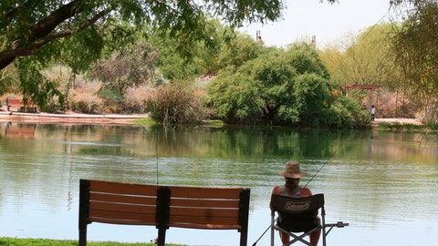 <p>               In this April 30, 2020 photo, a fisherman watches his line from the shade at Veterans Oasis Park in Chandler, Ariz. People who have been locked down during the coronavirus have been turning to fishing at community lakes as a chance to go outdoors and still following social-distancing guidelines. (AP Photo/John Marshall)             </p>