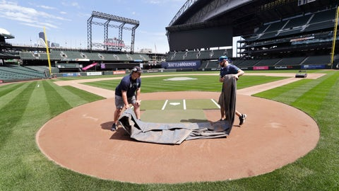 <p>               Grounds crew workers Jacob Weiderstrom, left, and Marcus Gignac pull a tarp off home plate as they continue to keep the Seattle Mariners' field in playing shape as the ballpark goes into its seventh week without baseball played because of the coronavirus outbreak Monday, May 11, 2020, in Seattle. A person familiar with the decision tells The Associated Press that Major League Baseball owners have given the go-ahead to making a proposal to the players' union that could lead to the coronavirus-delayed season starting around the Fourth of July weekend in ballparks without fans. (AP Photo/Elaine Thompson)             </p>