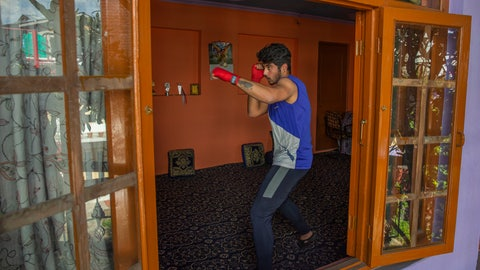 <p>               Kashmiri boxer Eyed Akeel Khan practices inside his house in Srinagar, Indian controlled Kashmir, April 23, 2020. Like many other athletes, the coronavirus pandemic has restricted Khan to his home. But lockdown for the 7 million residents of Kashmir is nothing new and the ongoing restrictions due to the pandemic is not the first time he has had to practice his sport at home. (AP Photo/Dar Yasin)             </p>