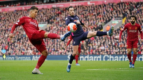 <p>               Liverpool's Roberto Firmino, left, challenges for the ball with Bournemouth's Adam Smith, center, as Liverpool's Mohamed Salah looks them during the English Premier League soccer match between Liverpool and Bournemouth at Anfield stadium in Liverpool, England, Saturday, March 7, 2020. (AP Photo/Jon Super)             </p>