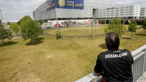 <p>               A lone fan of Fortuna Duesseldorf watches from far the Merkur Spiel-Arena prior to the Bundesliga soccer match between Duesseldorf and Paderborn in Duesseldorf, Germany, Saturday, May 16, 2020. The German Bundesliga becomes the world's first major soccer league to resume after a two-month suspension because of the coronavirus pandemic. (Roland Weihrauch/DPA via AP)             </p>