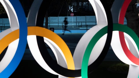 """<p>               FILE - In this March 30, 2020, file photo, a man jogs past the Olympic rings in Tokyo. Tokyo Olympic CEO Toshiro Muto talked Thursday, May 21, about the need to take """"countermeasures"""" to combat COVID-19 at next year's postponed games.  (AP Photo/Jae C. Hong, File)             </p>"""