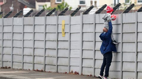 <p>               A man holds a child up over a fence to look into Liverpool's Melwood training ground after the English Premier League announced soccer players can return to training in small groups as the coronavirus lockdown was eased starting today Tuesday May 19, 2020. (Peter Byrne/PA via AP)             </p>