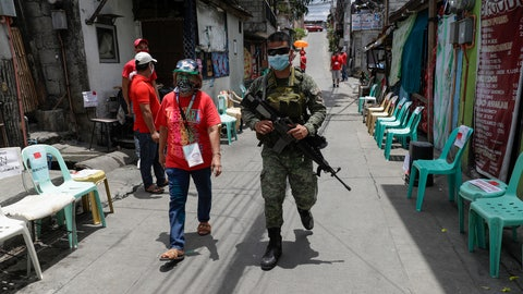 <p>               An army soldier walks with a volunteer as they wait for relief goods to be distributed and placed on chairs outside homes during a continuing enhanced community quarantine to prevent the spread of the new coronavirus in Quezon City, Metro Manila, Philippines on Monday, May 4, 2020. (AP Photo/Aaron Favila)             </p>