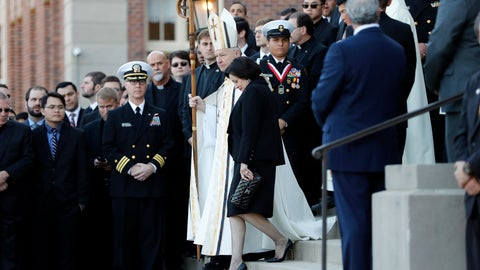 """<p>               FILE - In this March 21, 2018, file photo, Gayle Benson, widow of NFL New Orleans Saints and NBA New Orleans Pelicans owner Tom Benson, walks down the steps to receive his casket with New Orleans Archbishop Gregory Aymond for visitation at Notre Dame Seminary in New Orleans. Aymond, who knew the couple separately before they married in 2004, has become almost a part of the team, thought by some to bring the beloved Saints help from a higher power. Aymond was there to eulogize Tom Benson as a """"New Orleans saint on Earth"""" and walk side by side with Gayle in the funeral procession. (AP Photo/Gerald Herbert, File)             </p>"""