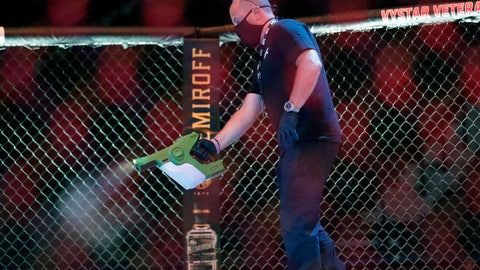 <p>               A worker sprays sanitizer in the octagon between bouts during a UFC 249 mixed martial arts competition, Saturday, May 9, 2020, in Jacksonville, Fla. (AP Photo/John Raoux)             </p>