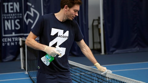 <p>               French veteran Nicolas Mahut cleans the net during a training session in the French Tennis Federation center near the grounds of the French Open in Paris, Wednesday, May 13, 2020 under the watchful eye of a team doctor and courtside trainers. Professional tennis players resumed training in France after the end of lockdown amid the coronavirus pandemic. (AP Photo/Francois Mori)             </p>