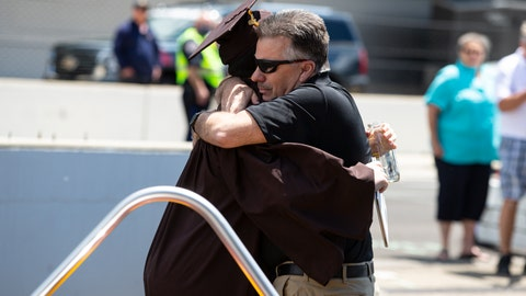 <p>               Ted Foxworthy, right, hugs his son Jacob Foxworthy as they walked off the track where he received his Speedway High School diploma during a ceremony at the Indianapolis Motor Speedway in Indianapolis, Saturday, May 30, 2020. The ceremony was held at the track to allow for social distancing requirements due to the COVID-19 pandemic. When Ted Foxworthy was diagnosed with cancer, he set two goals: Celebrating his youngest child's 18th birthday and seeing him graduate. (AP Photo/Michael Conroy)             </p>
