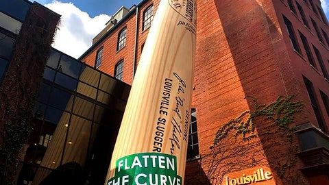 "<p>               In this April 7, 2020, photo provided by Louisville Slugger Museum & Factory, a ""Flatten the Curve"" banner adorns the 120-foot Big Bat outside Louisville Slugger Museum & Factory in Louisville, Ky., in an effort to help spread the ""stay healthy at home"" message and bring down the number of COVID-19 cases. (Louisville Slugger Museum & Factory via AP)             </p>"