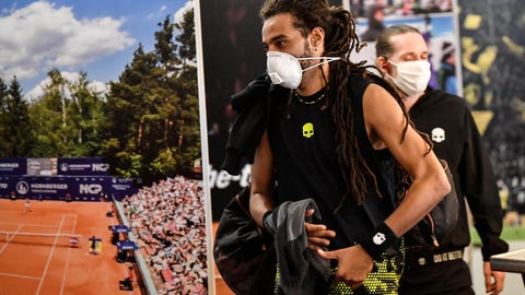 <p>               Germany's tennis player Dustin Brown wears a face mask as he walks by a poster at a pro-tennis tournament at a local base tennis academy in Hoehr-Grenzhausen, Western Germany, Friday, May 1, 2020. The professional tennis exhibition in the small village in the Westerwald is a rare exception to the global shutdown of sports during the coronavirus pandemic. Matches are played without line judges and without spectators, and broadcasted by remote cameras worldwide. (AP Photo/Martin Meissner)             </p>