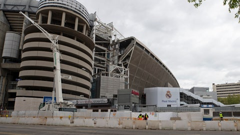 <p>               Constuction workers stand by Real Madrid's Santiago Bernabeu stadium in Madrid, Spain, Thursday, April 16, 2020. The Covid-19 coronavirus pandemic has affected more than games and player salaries for Real Madrid and Barcelona. It has also taken a toll on their stadium renovation plans. Both Spanish soccer clubs are working on hefty renovation projects for their famed venues.(AP Photo/Paul White)             </p>