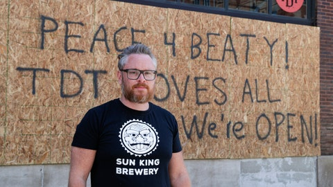 <p>               Restaurant owner Michael Cranfill poses in front of sign on the restaurant's boarded up windows in Indianapolis, Tuesday, June 2, 2020 to honor his friend former Indiana University football player Chris Beaty. Beaty was one of two people fatally shot in Indianapolis during protests over the death of George Floyd.(AP Photo/Michael Conroy)             </p>