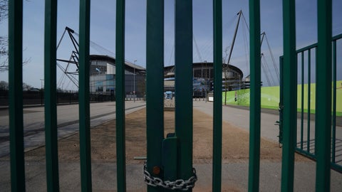 <p>               FILE - In this file photo dated Thursday, April 9, 2020, gates stand locked outside the closed English Premier League soccer Manchester City Etihad Stadium, in Manchester, northern England.  Guidance for sports bodies was published by the government on Saturday May 30, 2020, as COVID-19 lockdown restrictions are being eased further, allowing Sports events to resume in England from upcoming Monday, without any spectators and providing they comply with the government's coronavirus protocols. (AP Photo/Jon Super, FILE)             </p>