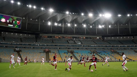 <p>               Players of Bangu, wearing white uniforms, and Flamengo play a Rio de Janeiro soccer league match at the Maracana stadium in Rio de Janeiro, Brazi, Thursday, June 18, 2020. Rio de Janeiro's soccer league resumed after a three-month hiatus because of the coronavirus pandemic. The match is being played without spectators to curb the spread of COVID-19. (AP Photo/Leo Correa)             </p>