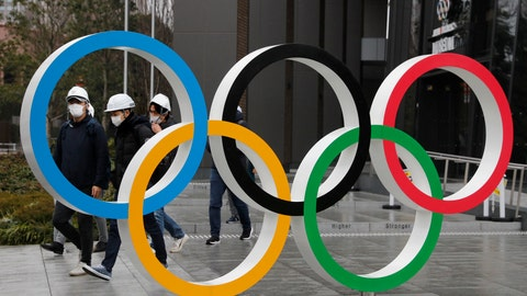 """<p>               FILE - In this March 4, 2020, file photo, people wearing masks walk past the Olympic rings near the New National Stadium in Tokyo. It's been 2 1/2 months since the Tokyo Olympics were postponed until next year because of the COVID-19 pandemic. So where do the games stand? So far, many ideas about how the Olympic can take place are being floated by the International Olympic Committee, Japanese officials and politicians, and in unsourced Japanese newspaper articles coming from local organizers and politicians. The focus is on soaring costs, fans, or no fans, possible quarantines for athletes, and cutting back to only """"the essentials."""" (AP Photo/Jae C. Hong, File)             </p>"""