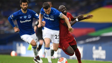 <p>               Everton's Seamus Coleman, left, challenges Liverpool's Sadio Mane during the English Premier League soccer match between Everton and Liverpool at Goodison Park in Liverpool, England, Sunday, June 21, 2020. (Peter Powell/Pool via AP)             </p>
