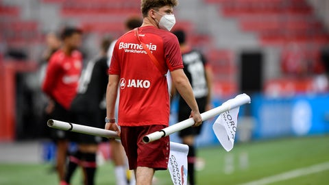 <p>               A ball boy carries the corner flags with a corona app commercial on it after the German Bundesliga soccer match between Bayer 04 Leverkusen and FSV Mainz 05 in Leverkusen, Germany, Saturday, June 27, 2020. Because of the coronavirus outbreak all soccer matches of the German Bundesliga take place without spectators. (AP Photo/Martin Meissner, Pool)             </p>