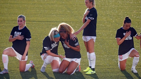 <p>               Chicago Red Stars' Julie Ertz, second from left, holds Casey Short, center, while other players for the team kneel during the national anthem before an NWSL Challenge Cup soccer match against the Washington Spirit at Zions Bank Stadium, Saturday, June 27, 2020, in Herriman, Utah. (AP Photo/Rick Bowmer)             </p>