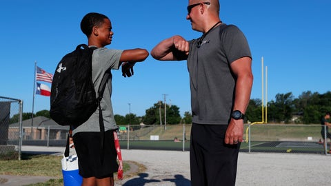 <p>               Head football coach Bob Wager, right, and sophomore safety Cameron Conley greet each other at the re-opening of strength and conditioning camp at Arlington Martin High School, Thursday, June 18, 2020, in in Arlington, Texas. While states have been easing the economic and social lockdowns prompted by the coronavirus pandemic, some are now letting high school athletes return for summer workouts before teachers have even figured out how they are going to hold classroom instruction. (AP Photo/LM Otero)             </p>