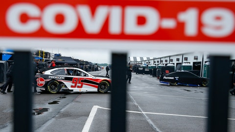 <p>               Crew members are visible under a COVID-19 alert sign as they push the car of Christopher Bell through the garage area in the morning before a scheduled NASCAR Cup Series auto race at Pocono Raceway, Saturday, June 27, 2020, in Long Pond, Pa. (AP Photo/Matt Slocum)             </p>