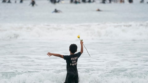 "<p>               Nathan Rangel, 11, jumps in the water carrying a rose as surfers participate in a paddle out ceremony at ""The Ink Well,"" a beach historically known as a surfing refuge for African Americans, to honor the life of George Floyd on Friday, June 5, 2020, in Santa Monica, Calif. Floyd died after he was restrained in police custody on Memorial Day in Minneapolis. (AP Photo/Ashley Landis)             </p>"