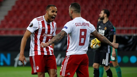 <p>               FILE - In this Thursday, March 12, 2020 file photo, Olympiakos' Youssef El-Arabi, left, celebrates with Guilherme after scoring his side's opening goal during the Europa League round of 16 first leg soccer match between Olympiakos and Wolverhampton Wanderers at the Karaiskakis Stadium in Piraeus, Greece. Soccer restarts in Greece this weekend with the fierce rivalry between a runaway league leader and defending champion playing out on the field and in a court in Switzerland. Unbeaten Olympiakos travels to second-place PAOK on Sunday June 4, 2020, in the first Super League championship round _ a new, 10-round playoff for the top six in the regular season table. (AP Photo/Thanassis Stavrakis, File)             </p>