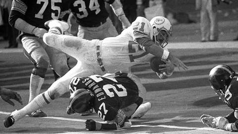 """<p>               FILE - In this Dec. 31, 1972, file photo, Miami Dolphins Jim Kiick goes headfirst over Pittsburgh Steelers"""" Glen Edwards as Kiick scores in third quarter of the AFC championship game at Pittsburgh's Three Rivers Stadium.  Former running back Kiick, who helped the Dolphins achieve the NFL's only perfect season in 1972, has died at age 73. In recent years Kiick battled memory issues and lived in an assisted living home, and the team announced his death Saturday, June 20, 2020. (AP Photo, File)             </p>"""