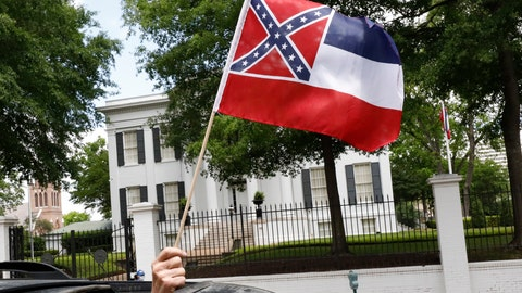 """<p>               In this April 25, 2020 photograph, a small Mississippi state flag is held by a participant during a drive-by """"re-open Mississippi"""" protest past the Governor's Mansion, in the background, in Jackson, Miss. This current flag has in the canton portion of the banner the design of the Civil War-era Confederate battle flag, that has been the center of a long-simmering debate about its removal or replacement. (AP Photo/Rogelio V. Solis)             </p>"""