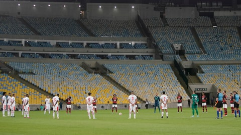 <p>               Players of Bangu, wearing white uniforms, and Flamengo pay a minute of silence for the victims of the coronavirus prior to a Rio de Janeiro soccer league match at the Maracana stadium in Rio de Janeiro, Brazi, Thursday, June 18, 2020. Rio de Janeiro's soccer league resumed after a three-month hiatus because of the coronavirus pandemic. The match is being played without spectators to curb the spread of COVID-19. (AP Photo/Leo Correa)             </p>