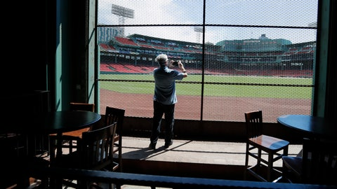 <p>               In this June 25, 2020, photo, a reporter photographs the view of the baseball field at Fenway Park from the Bleacher Bar in Boston. Tucked under the center field seats at Fenway Park, down some stairs from Lansdowne Street in an area previously used as the visiting team's batting cage, is a sports bar that is preparing to reopen from the coronavirus shutdown. If Major League Baseball's plans remain on schedule, it may be one of the few places fans will be able to watch a game in person this season. (AP Photo/Elise Amendola)             </p>