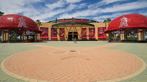 <p>               People walk by the front of Angel Stadium, Thursday, June 25, 2020, in Anaheim, Calif. By the time Major League Baseball returns in late July, it will have been more than four months since teams last played. The season is now going to be a 60-game sprint to the finish, held in ballparks without fans and featuring some unusual rules. (AP Photo/Mark J. Terrill)             </p>