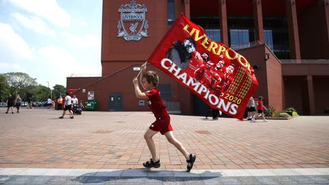 <p>               Liverpool fan Dillon Parry waves a flag outside Anfield in Liverpool, England, Friday June 26, 2020. Liverpool clinched its first league title since 1990 on Thursday, ending an agonizing title drought. (Martin Rickett/PA via AP)             </p>