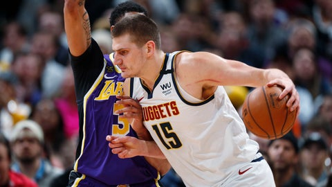 <p>               FILE - In this Feb. 12, 2020, file photo, Denver Nuggets center Nikola Jokic drives as Los Angeles Lakers forward Anthony Davis defends during the first half of an NBA basketball game in Denver. A person with knowledge of the situation says Jokic has tested positive for the coronavirus and is quarantining in his native Serbia. (AP Photo/David Zalubowski, File)             </p>