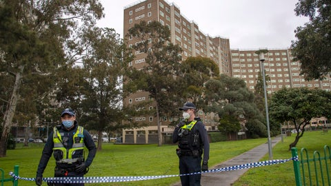 <p>               Police guard access to housing commission apartments under lockdown in Melbourne, Australia, on Monday, July 6, 2020. The hard-hit Australian state of Victoria recorded two deaths and its highest-ever daily increase in coronavirus cases on Monday as authorities prepare to close its border with New South Wales. (AP Photo/Andy Brownbill)             </p>