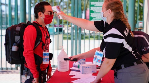 <p>               Ricardo Zapata, left, a photographer for the Los Angeles Angels, has his temperature taken by Sarah Morris before entering Angels Stadium for baseball practice on Monday, July 6, 2020, in Anaheim, Calif. New protocols like temperature checks, social distancing, and limiting amount of people allowed in sports venues have been put in place due to the spread of COVID-19. (AP Photo/Ashley Landis)             </p>