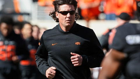 <p>               FILE - In this Nov. 2, 2019, file photo, Oklahoma State coach Mike Gundy runs onto the field before the team's NCAA college football game against TCU in Stillwater, Okla. Hubbard said on Twitter that he won't do anything with the program until there is change after Gundy was photographed wearing a T-shirt representing far-right online publication One America News Network. Gundy is seen in a photograph on Twitter wearing the T-shirt with the letters OAN. (AP Photo/Sue Ogrocki, File)             </p>