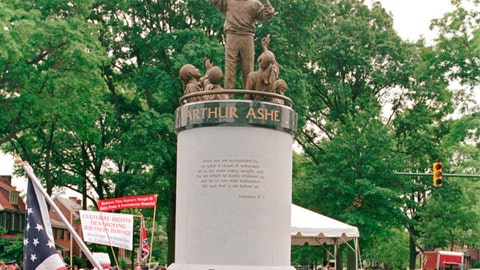 """<p>               FILE - In this July 10, 1996 file photo, a crowd gathers at the base of the Arthur Ashe Monument after the ceremony dedicating the statue on Monument Avenue in Richmond, Va.  The statue of the African American tennis legend has been vandalized with the words """"White Lives Matter."""" Richmond Police said they were alerted to the vandalism Wednesday, June 17, 2020. Police say red paint on the statue itself was already being cleaned off by community members. (AP Photo/Steve Helber)             </p>"""