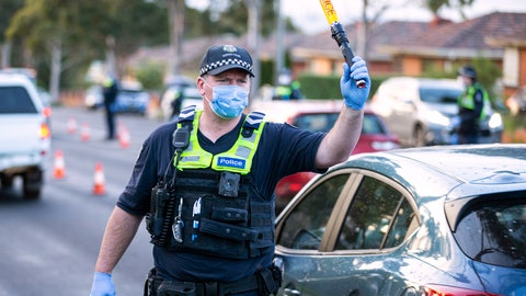 <p>               A police officer directs traffic at a roadblock in suburban Melbourne, Australia, Thursday, July 2, 2020. Thousands of residents in dozens of suburbs of Melbourne, are preparing to lockdown for a month with the Victoria state premier warning a state-wide shutdown is possible if coronavirus cases continue to rise. (Daniel Pockett/AAP Image via AP)             </p>