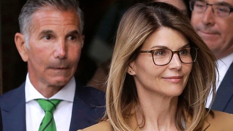 <p>               FILE - In this April 3, 2019, file photo, actress Lori Loughlin, front, and her husband, clothing designer Mossimo Giannulli, left, depart federal court in Boston after a hearing in a nationwide college admissions bribery scandal. In a court filing on Monday, July 13, 2020, lawyers for the couple, who admitted to paying $500,000 to get their daughters into the University of Southern California as fake crew recruits, asked a judge to lower their bail from $1 million to $100,000, saying they will not flee ahead of their August sentencing in the college admissions bribery case. (AP Photo/Steven Senne, File)             </p>