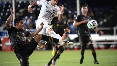 <p>               LA Galaxy forward Cristian Pavon, center, attempts to shoot on goal as Los Angeles FC defender Eddie Segura, left, defends during the first half of an MLS soccer match Saturday, July 18, 2020, in Kissimmee, Fla. (AP Photo/Phelan M. Ebenhack)             </p>