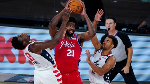 <p>               Washington Wizards center Thomas Bryant (13) and guard Jerome Robinson (12) tries to tie up Philadelphia 76ers center Joel Embiid (21) during the second half of an NBA basketball game Wednesday, Aug. 5, 2020 in Lake Buena Vista, Fla. (AP Photo/Ashley Landis)             </p>