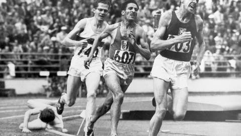"""<p>               FILE - In this July 24, 1952, file photo, British athlete Christopher """"Chris"""" Chataway falls as Emil Zatopek of Czechoslovakia, followed by Alain Mimoun of France and German bronze medal winner Herbert Schade, leads near the end of the Men's final 5000 meter race at the Summer Olympic Games on in Helsinki, Finland. (AP Photo/File)             </p>"""