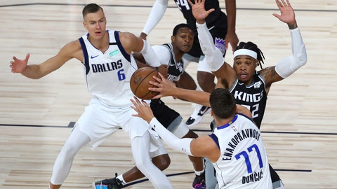 <p>               Dallas Mavericks guard Luka Doncic (77) passes the ball to forward Kristaps Porzingis (6) as Sacramento Kings center Richaun Holmes (22) defends during the first half of an NBA basketball game Tuesday, Aug. 4, 2020, in Lake Buena Vista, Fla. (Kim Klement/Pool Photo via AP)             </p>
