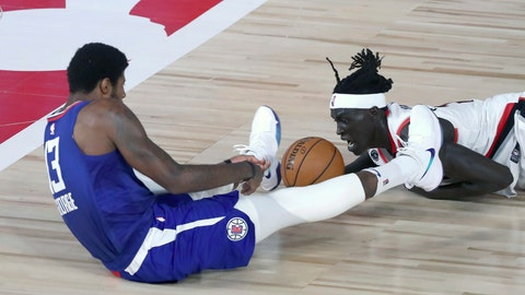 <p>               Los Angeles Clippers guard Paul George (13), left, and Portland Trail Blazers forward Wenyen Gabriel (35) battle for a loose ball during the first half of an NBA basketball game Saturday, Aug. 8, 2020, in Lake Buena Vista, Fla. (Kim Klement/Pool Photo via AP)             </p>