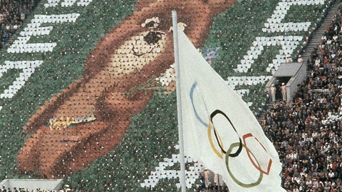 <p>               FILE - In this July 19, 1980, file photo, members of the crowd hold up 3,500 cards to create an image of Misha the Bear Cup, the mascot of the Moscow Olympic Games at the Lenin Stadium in Russia on. Above burns the Olympic flame. (AP Photo/File)             </p>