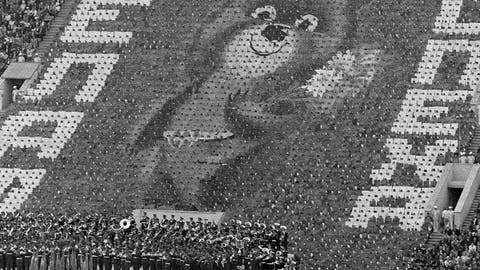 <p>               FILE - In this July 19, 1980, file photo, a giant image of Misha, the Russian bear mascot of the 1980 Moscow Summer Olympic Games, greets athletes standing on the field of Moscow's Lenin Stadium during opening ceremonies of the competitions in Moscow. The image was created by 3,500 card-bearers. Overhead burns the Olympic flame. (AP Photo/File)             </p>